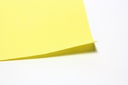 Yellow note with clip on white background photo