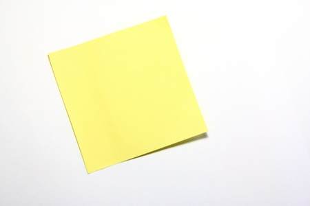 Yellow note with clip on white background Stock Photo