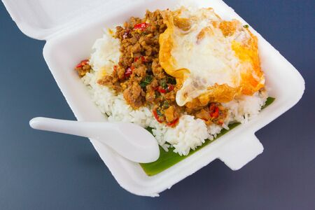 Rice topped with stir-fried pork and basil on foam box