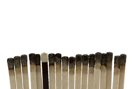 A black and unburnt matchsick among a line of burnt matchsticks against a white background photo