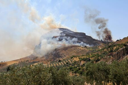 threatens: Forest fire on the mountain that threatens crops and residential areas