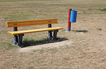 Yellow bench and blue recycle bin in the park photo