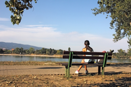 A young girl sitting on a bench and looking at the lake