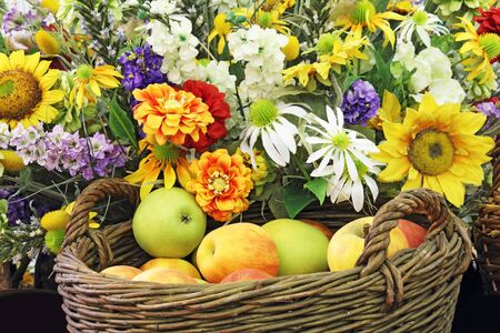 Basket full of apples and lots of flowers photo