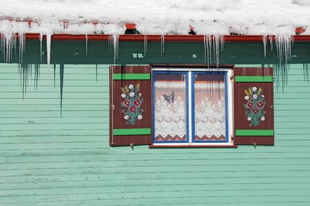 Wooden window farmhouse hand painted under the roof full of snow photo