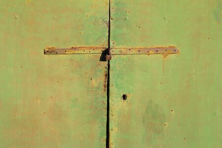 hasp: Old and rusty metal green, door, locked with  iron hasp