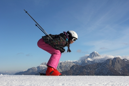 The young girl on skis in the background of mountains covered with snow photo