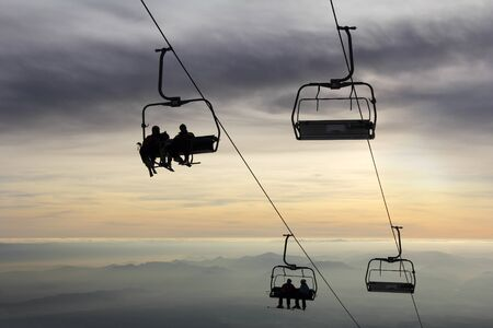 Ski-lift transports skiers to the top of the mountain and the sun goes down photo