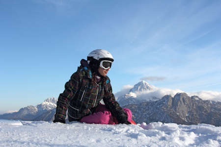 A young girl sitting on the snow in front of the mountains photo