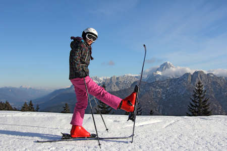 The young girl on skis in front of mountains   photo