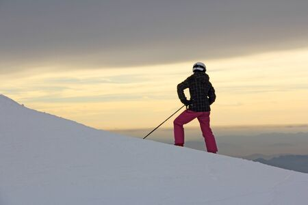 The silhouette of girls on skis on the mountain photo