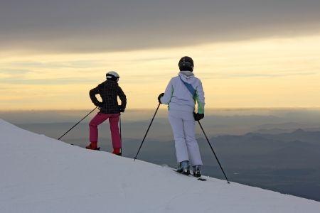Silhouettes two girls on skis on the mountain