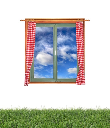 Window with a view of the clouds and green grass isolated on white background photo