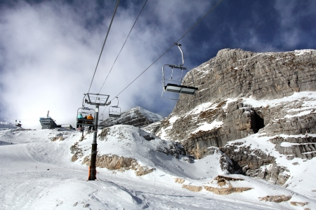 Ski-lift transports skiers to the top of the mountain  on a lovely, sunny winter day photo