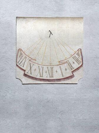 reloj de sol: Antiguo reloj de sol de tablas de piedra en la pared gris