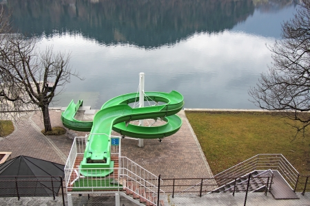 Green water slide, on the lake shore photo