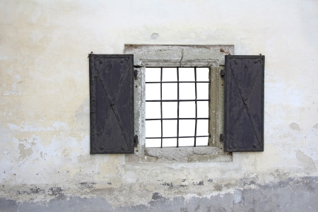 Old stone window with iron bars and gates photo