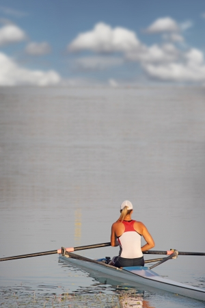scull: A young woman in a boat ready to start waiting in rowing race