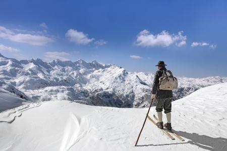 Old Skifahrer mit traditionellen alten hölzernen Ski und Rucksack
