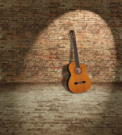 Old wooden guitar leaning against the brick wall Stockfoto