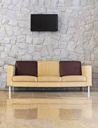 seater: Leather sofa in front of the stone wall