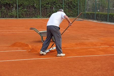 tennis clay: A worker fixes the lines on tennis courts Stock Photo