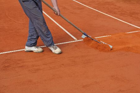 A worker fixes the lines on tennis courts photo