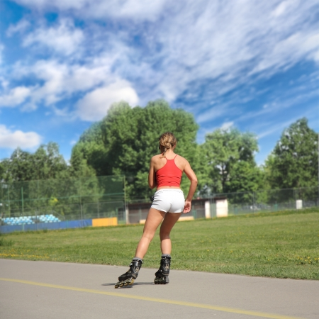 Pretty girl goes on roller skates on a beautiful sunny day photo