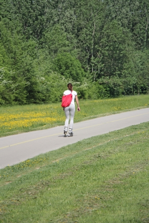 rollerskating: Pretty girl goes on roller skates on a beautiful sunny day