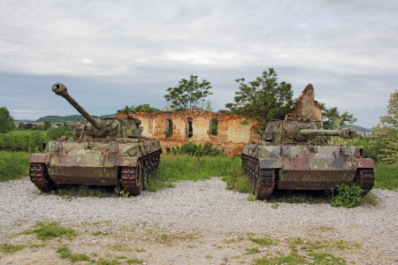 Two old tank in front of ruined brick building photo