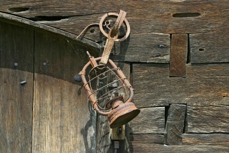 Rusty old lamp hanging on the wooden wall of the barn photo