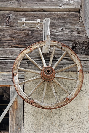 Old wooden wheel hanging on a wooden wall of the barn photo