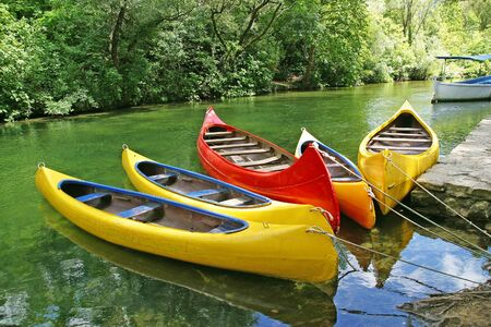 camping equipment: Five empty plastic canoes in turquoise green river