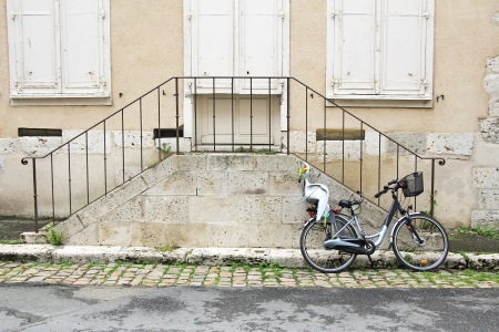 bicycle with child seat, leaning against the old stone stairs photo