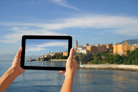 Girl taking pictures on a tablet in Bastia, Corsica, France  Stock Photo