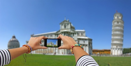 Girl taking pictures on a mobile phone in the Cathedral and Leaning Tower of Pisa photo