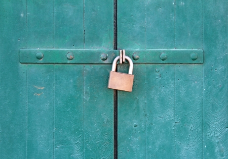 old green wooden door locked with a padlock photo