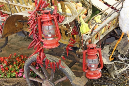 red oil lamp: Old red lanterns apples and pumpkins on a wooden carriage