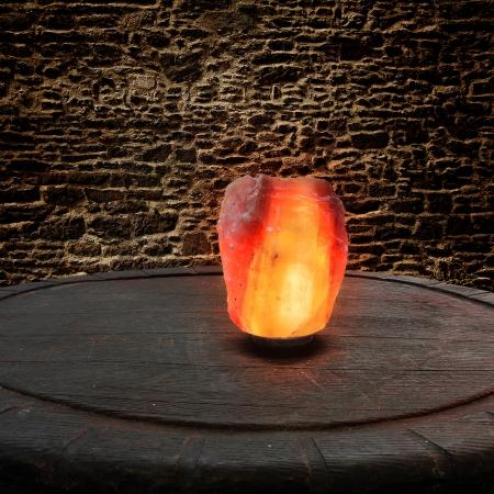 Sale dell'Himalaya come una lampada su un vecchio tavolo di legno di fronte a un muro di pietra
