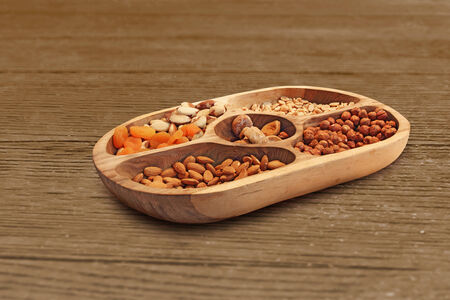 Hazelnuts, almonds and other different dried fruits in a wooden bowl  photo