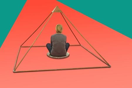 Woman meditating and making yoga in metal pyramid Stock Photo - 23646858