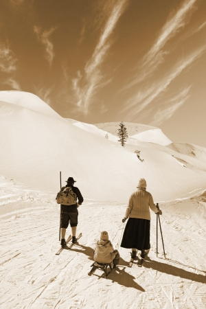 Man and woman with old wooden skis and child on sled on snowy mountain photo