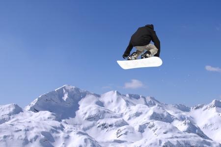 Snowboarder a saltare inhigh montagne a giornata di sole Archivio Fotografico