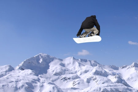 Snowboarder bei Sprung hoch Berge am sonnigen Tag Lizenzfreie Bilder