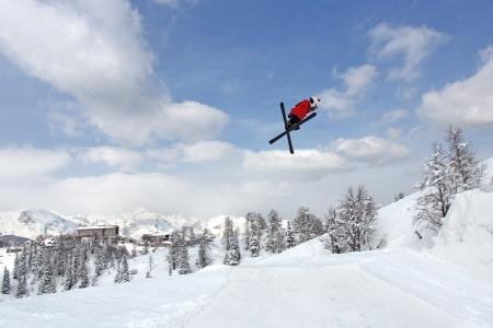 slovenia: Jumping skier at jump inhigh mountains at sunny day