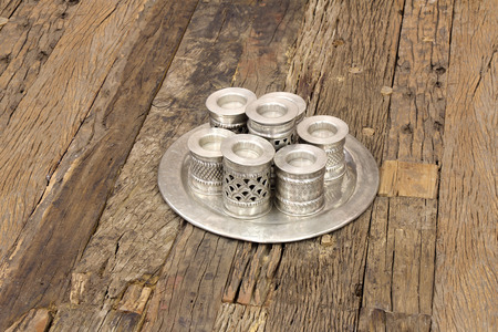 candle holders: Old handmade silver candlestick on a wooden background Stock Photo