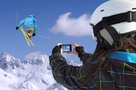 A young girl by mobile phone photographs of skiers jump