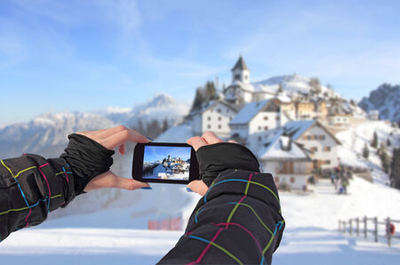 Photographing by cell phone of winter landscape in idyllic village Monte Lussari, Italy Stockfoto