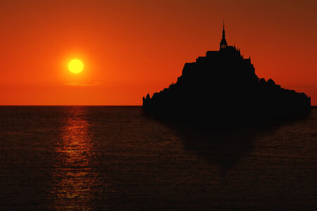 Le Mont Saint Michel silhouette with reflection in Normandy, France at sunset photo