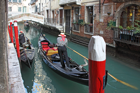 canal parade: Gondolas transporting tourists in one of the many canals of Venice